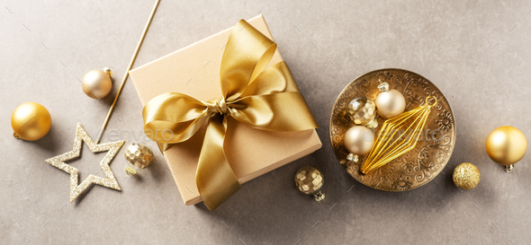 Gift box with golden ribbon on grey background - Stock Photo - Images