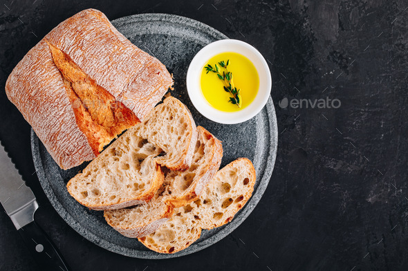 Italian ciabatta bread slices with olive oil on stone plate on dark concrete background - Stock Photo - Images