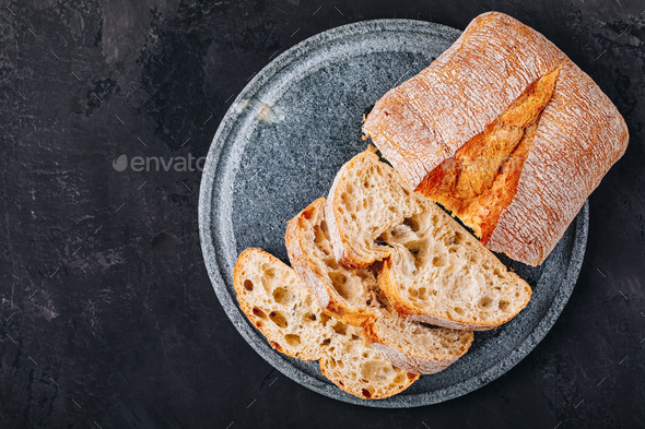 Italian ciabatta bread slices with on stone plate on dark concrete background - Stock Photo - Images