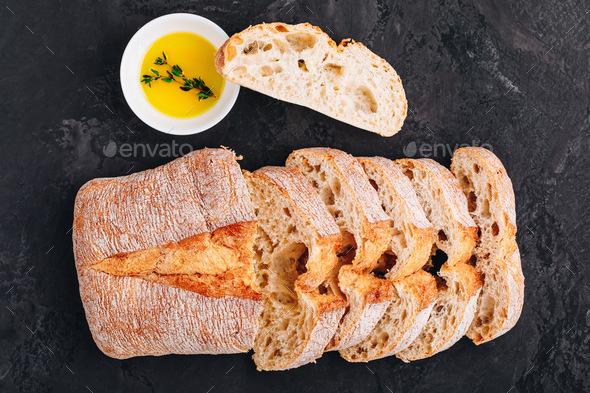 Italian ciabatta bread slices with olive oil on dark stone concrete background - Stock Photo - Images