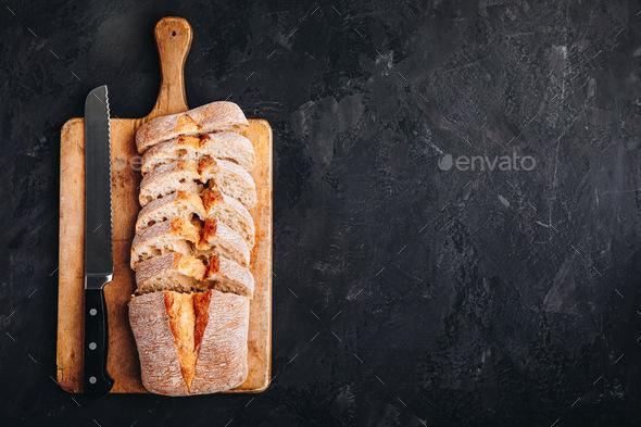 Italian ciabatta bread slices on wooden chopping board on dark stone concrete backdrop - Stock Photo - Images