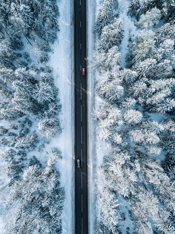 Aerial view of winter road and forest with snow covered trees in Finland - Stock Photo - Images