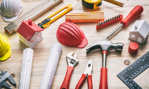 Tools, hardhats and project plans on wooden desk - Stock Photo - Images
