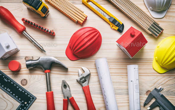 Tools, hardhats and project plans on wooden desk, top view. - Stock Photo - Images