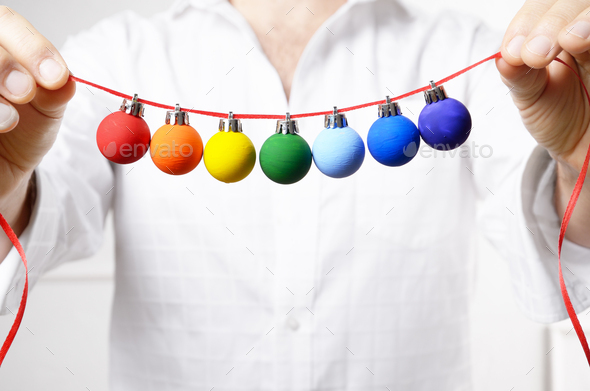 Middle aged caucasian male model in unbuttoned shirt hold painted Christmas balls. Space for text - Stock Photo - Images