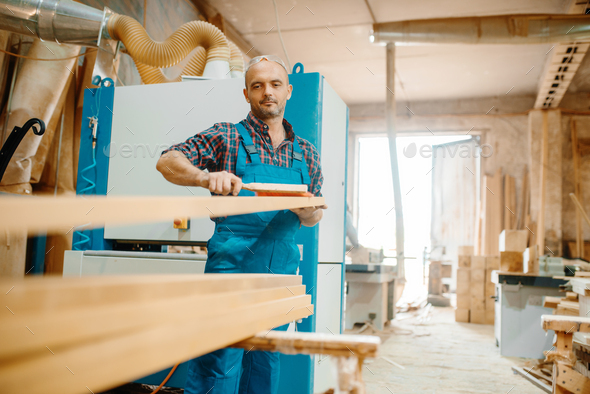 Carpenter processes board on plane machine - Stock Photo - Images