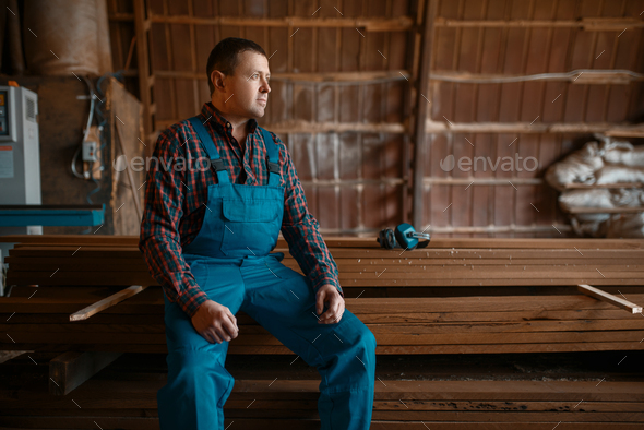 Joiner in uniform at his workplace on timber mill - Stock Photo - Images