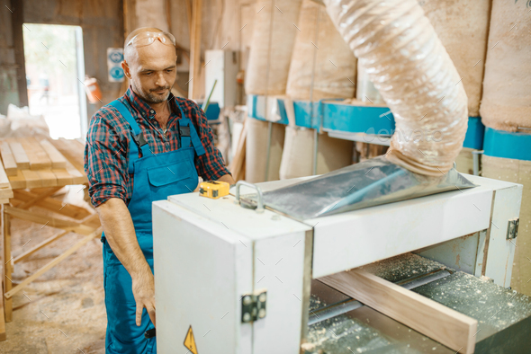 Carpenter works on plane machine, woodworking - Stock Photo - Images
