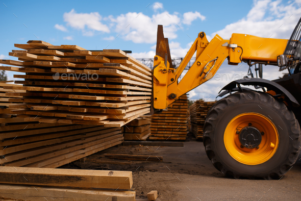 Forklift loads the boards in the lumber yard - Stock Photo - Images