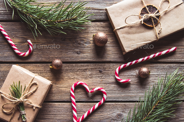 Christmas gifts for new year wrapped in craft paper near branches and cones on wooden background - Stock Photo - Images