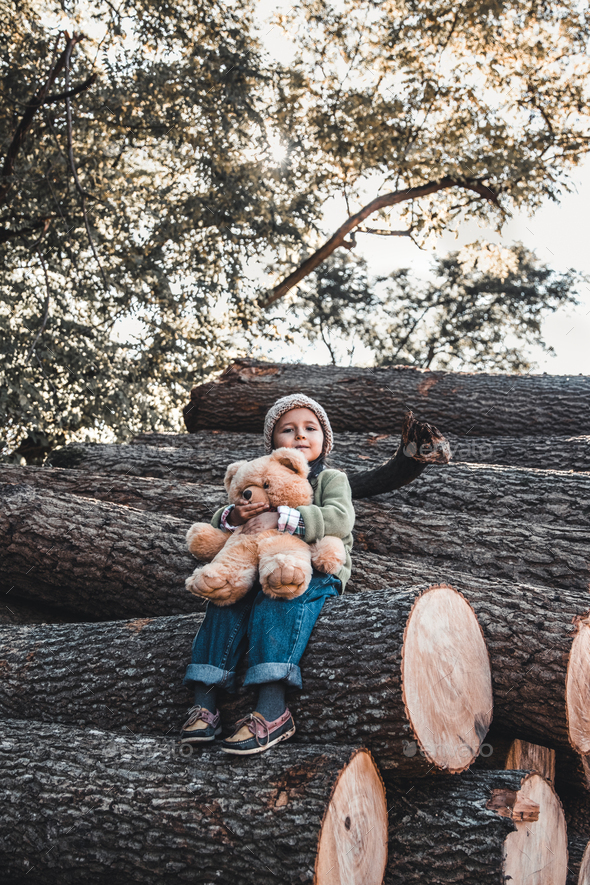 Little girl with a teddy bear sitting on logs - Stock Photo - Images