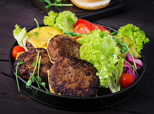 Burger cooking - burger with beef,  tomato, cheese, pickled cucumber and red onion on plate - Stock Photo - Images