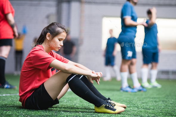 Sad or tired female football player in sports uniform sitting on green field - Stock Photo - Images