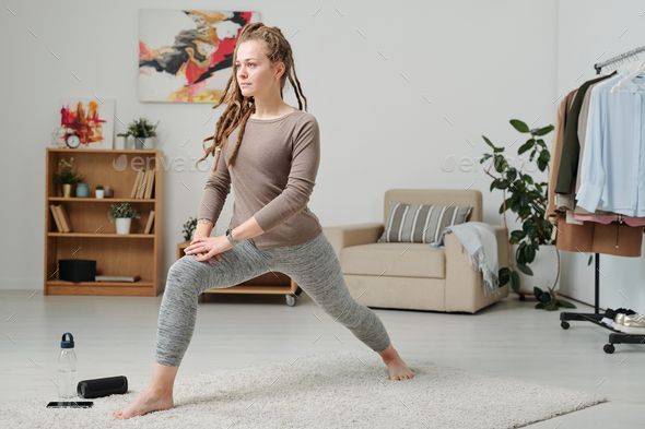 Young barefoot woman in activewear stretching legs while exercising on carpet - Stock Photo - Images