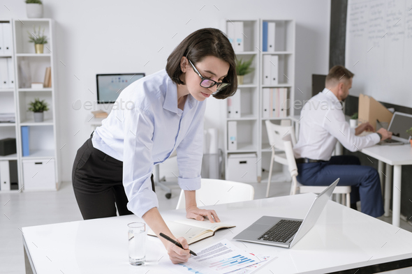 Young brunette businesswoman bending over desk while reading paper - Stock Photo - Images