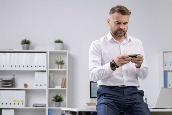 Serious office worker in formalwear watching video in smartphone or messaging - Stock Photo - Images