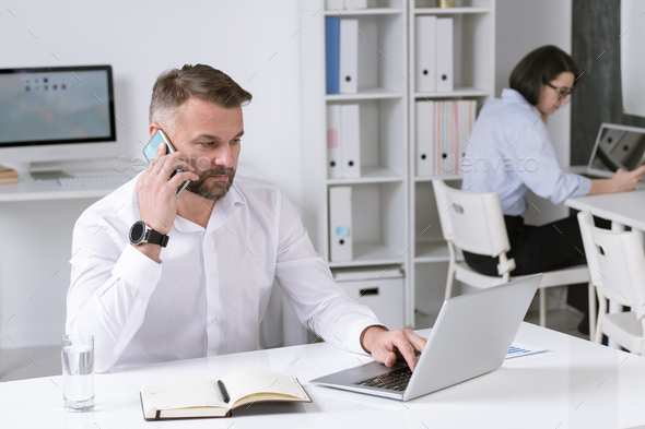Serious mature businessman with smartphone talking to business partner - Stock Photo - Images