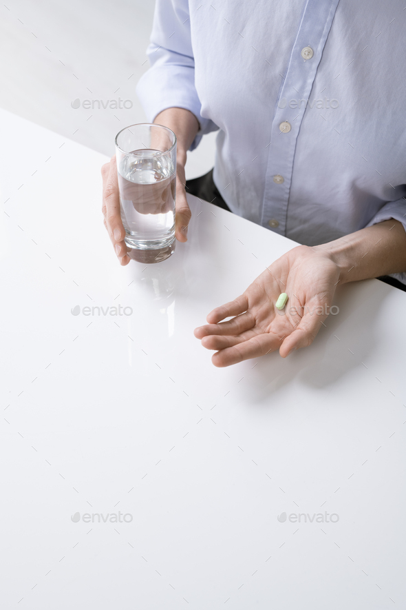 Hands of sick female or businesswoman going to have glass of water and pill - Stock Photo - Images