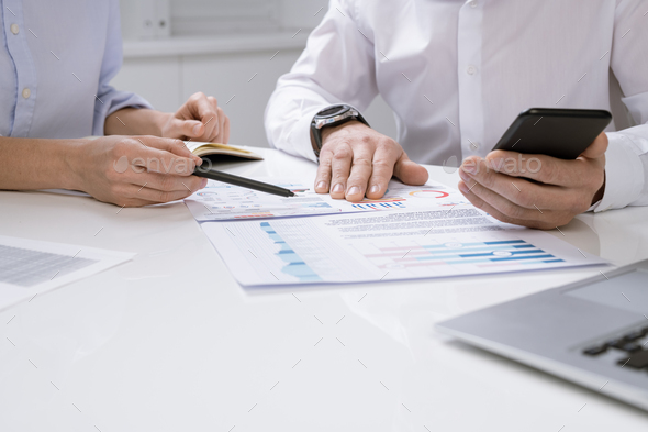 Hands of contemporary economists discussing financial chart on paper - Stock Photo - Images