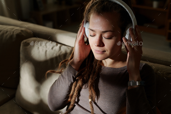 Calm female with headphones enjoying music for sleep while sitting on couch - Stock Photo - Images