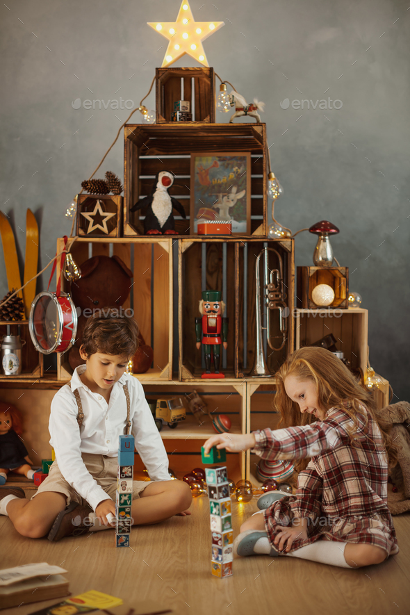Two Kids Playing With Toys Near the Christmas Tree - Stock Photo - Images
