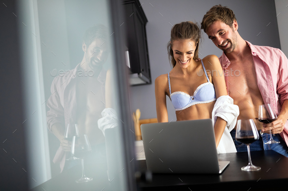 Young couple relaxing in kitchen with wine and laptop. Love, technology, people concept - Stock Photo - Images
