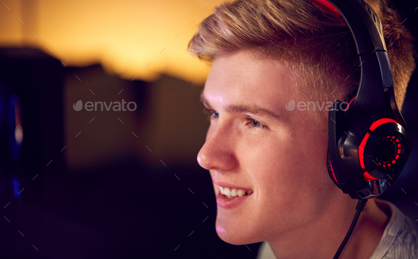 Teenage Boy Wearing Headset Gaming At Home Using Dual Computer Screens - Stock Photo - Images