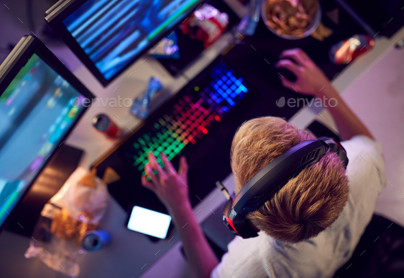 Overhead View Of Teenage Hacker Sitting In Front Of Computer Screens Bypassing Cyber Security - Stock Photo - Images