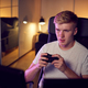 Teenage Boy With Game Pad Sitting In Chair and Gaming At Home - PhotoDune Item for Sale