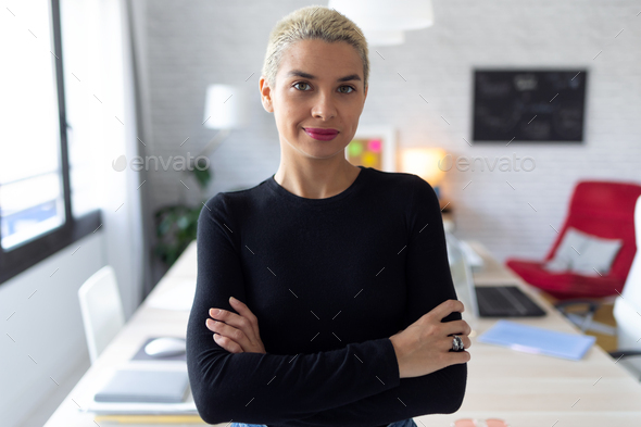 Modern young entrepreneur woman looking at camera while standing in the office. - Stock Photo - Images
