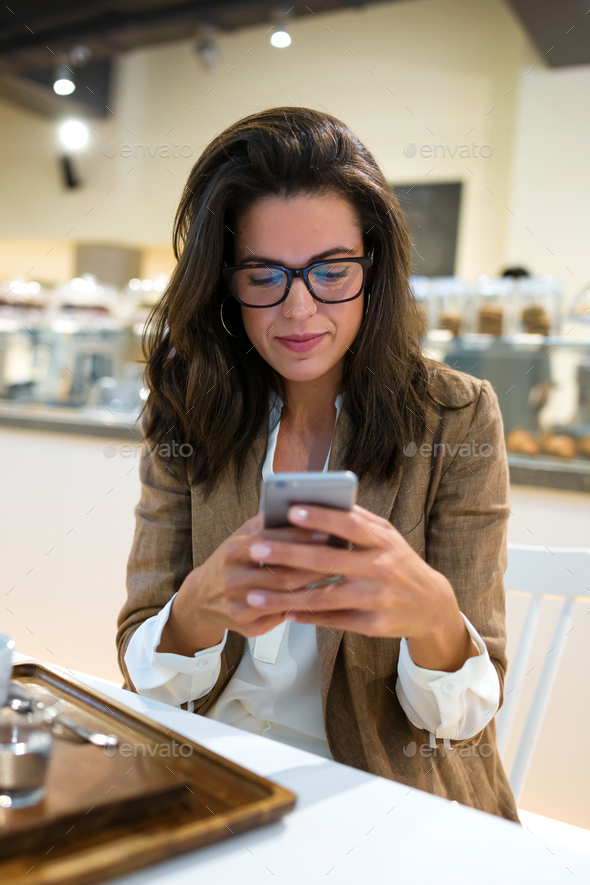 Beautiful young businesswoman with eyeglasses texting with her mobile phone in the coffee shop. - Stock Photo - Images
