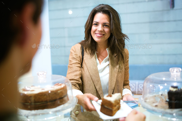 Beautiful young businesswoman buying portion of delicious homemade carrot cake in the coffee shop. - Stock Photo - Images