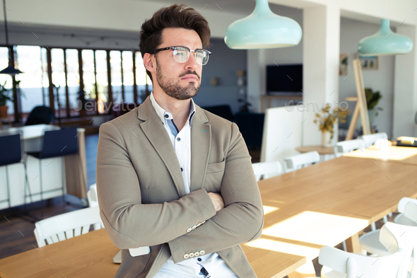 Handsome young business man looking sideways while sitting on table in the office. - Stock Photo - Images