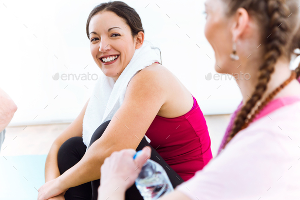 Couple relaxing on yoga mat and talking after workout session. - Stock Photo - Images