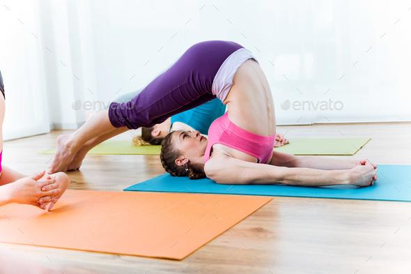 Group of people practicing yoga at home. Halasana pose. - Stock Photo - Images