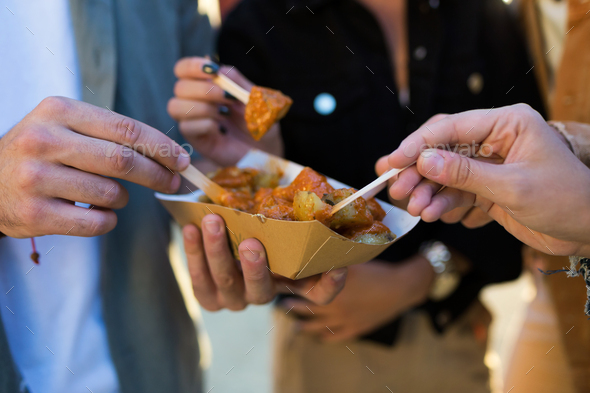 Group of friends visiting eat market and eating potatoes in the street. - Stock Photo - Images