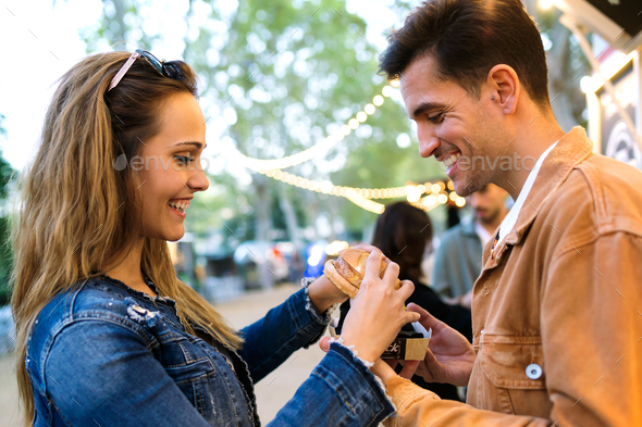 Lovely attractive couple sharing and eating hamburger together in eat market in the street. - Stock Photo - Images