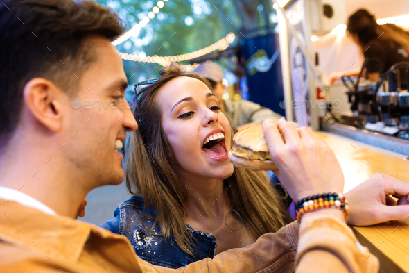 Attractive young man giving hamburger to his beautiful girlfriend in eat market in the street. - Stock Photo - Images