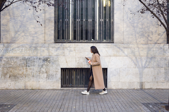 Pretty young woman using her mobile phone while walking in the street. - Stock Photo - Images