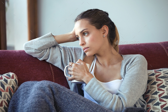 Depressed young woman thinking about her problems while drinking coffee on sofa at home. - Stock Photo - Images