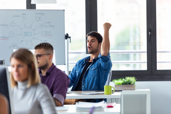 Successful young businessman celebrating something while working with laptop in the office. - Stock Photo - Images