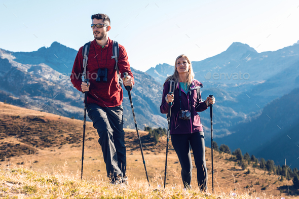 Two travel hikers with backpack walking while looking the landscape in the mountain. - Stock Photo - Images