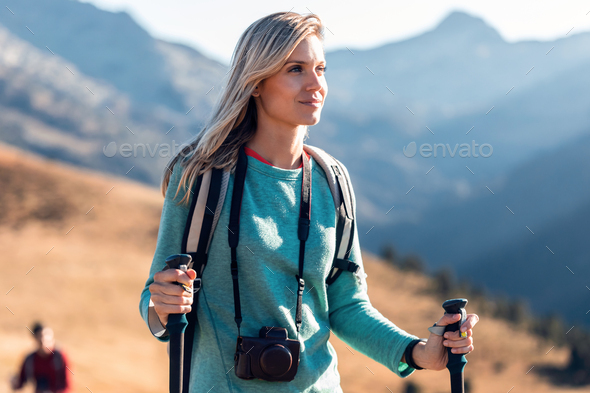 Pretty young woman traveler with backpack looking to the side while walking on mountain. - Stock Photo - Images