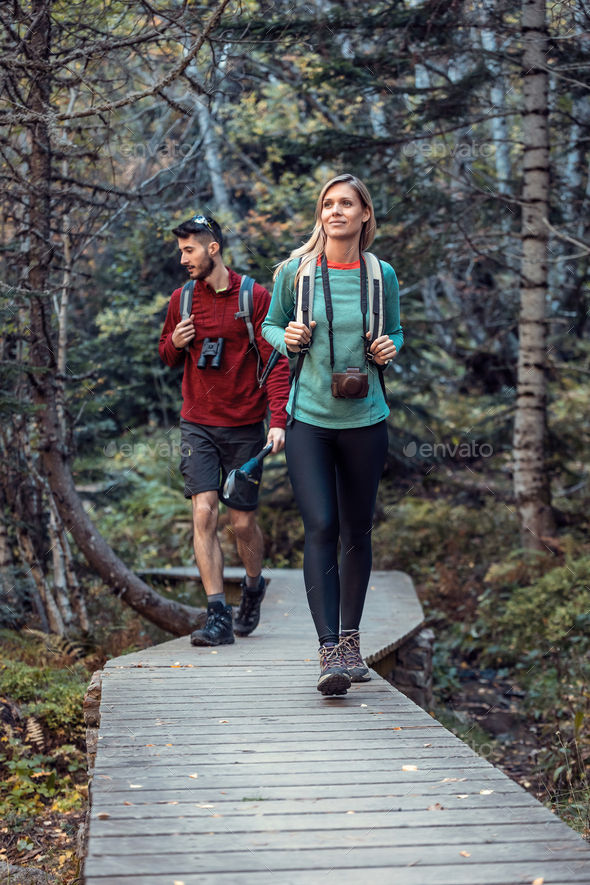 Two travel hikers with backpack walking while looking the landscape in the forest. - Stock Photo - Images