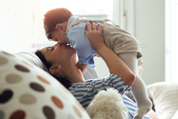 Pretty young mother with her baby playing and loving in the living room at home. - Stock Photo - Images