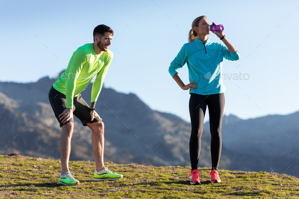 Healthy young couple relaxing after running while the woman drinks water on the mountain. - Stock Photo - Images