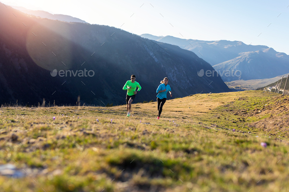 Healthy young couple running on mountain trail in the morning. - Stock Photo - Images