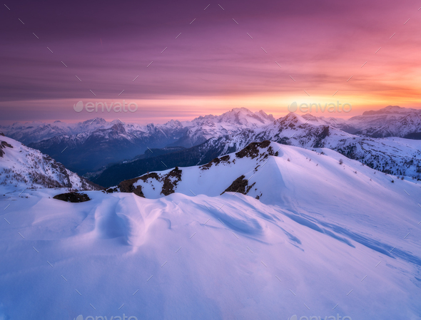 Colorful red sky and sunlight over the snow covered mountains - Stock Photo - Images