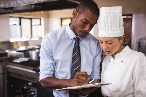 Male manager and female chef writing on clipboard in kitchen - Stock Photo - Images