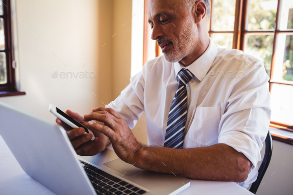 Businessman using mobile phone at the table - Stock Photo - Images
